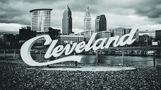 Cleveland Ohio skyline in black and white with sculpture of the word Cleveland in the foreground.