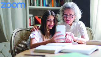 Elderly woman and young child looking at cell phone while sitting at table with books.